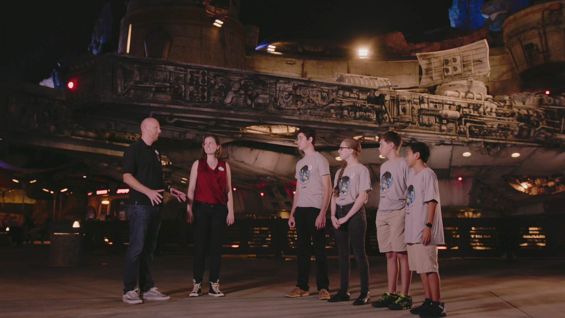 FIRST students standing in front of the Millennium Falcon with Disney Imagineers